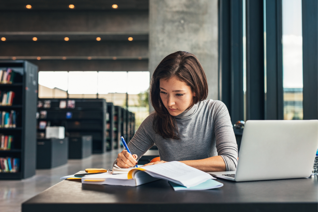 Woman writing research in library